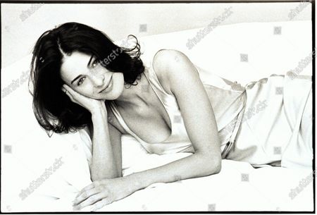 Socialite, novelist and contributing editor to Vogue, Marina Rust, wearing a sleeveless slip dress by Calvin Klein, smiling and lying in a bed, supporting her head in her hand. Marina Rust Connor