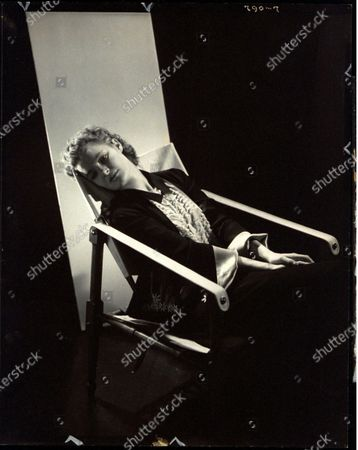 Actress, Linda Watkins, wearing a black dress, with white cuffs, sitting in an armchair, looking away from the camera. Linda Watkins