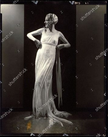 Dancer and blues singer, Frances Williams, with wavy short blond hair, wearing a sleeveless floor-length white dress, standing with both hands on her hips, and head turned to the side. Frances Williams