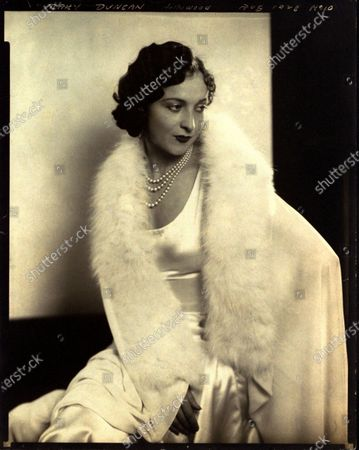 Actress, Mary Duncan, seated with head turned to side and looking to far side, one hand splayed across lap; wearing a white satin dress, white silk cape with white fur, and a three-strand pearl necklace; hair in a short wavy bob. Mary Duncan