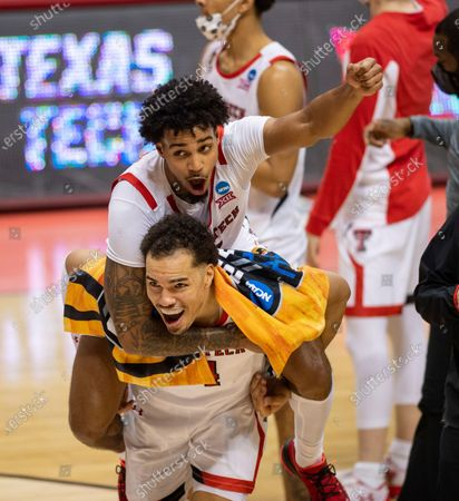 Texas Tech guard Kyler Edwards (11) catches a ride on the back of teammate forward Marcus Santos-Silva (14) as the two celebrate their win over Utah State in a first round game in the NCAA men's college basketball tournament, at Assembly Hall in Bloomington, Ind