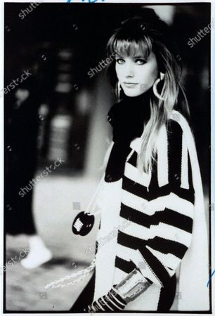 Close-up of model Cecilia Chancellor, with long hair tapered around the face, with brow-length bangs, wearing a striped sweater, and large hoop earrings. Cecilia Chancellor