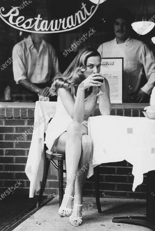 Model Tatjana Patitz wearing a shift in white lace, by Carolina Herrera, with sheer white stockings, and strappy high-heeled sandals, sitting at an outdoor cafe, drinking a glass of red wine. Tatjana Patitz