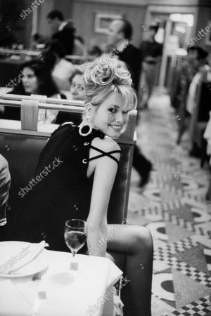 Model Claudia Schiffer seated at a booth sideways, wearing a wool crepe dress with silver grommets and shoulder lacing. Claudia Schiffer