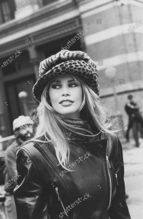 Model, Claudia Schiffer, wearing a stretch-back black leather jacket, by Escada Margaretha Ley, with a zebra print beret over a brimmed leopard print hat, by Marie Mercie, standing on a street with pedestrians and a subway station in the background. Claudia Schiffer