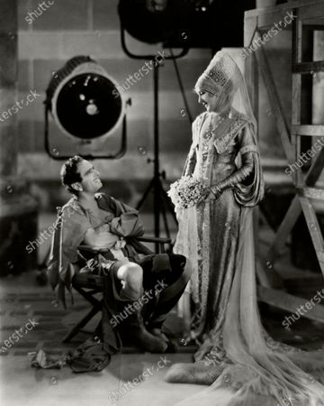 Married acting couple, Douglas Fairbanks, sitting in a director chair, and Mary Pickford, standing in front of him, both wearing costumes, on the movie set of the Taming of the Shrew, with lights and a prop in background. Douglas Fairbanks Sr., Mary Pickford