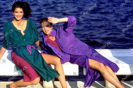Model Janice Dickinson, left, and her sister Deborah Dickinson, right, sit on the edge of a pier in Boca Raton, Florida, leaning back on their hands as Deborah shields her face from the setting sun. Janice is wearing green button front tunic and magenta skirt with American Indian Arts Center earrings. Deborah is wearing a purple button-front blouse and purple skirt with a magenta collarless shirt and Celia Sebiri earrings. Both ensembles in silk crepe de Chine by Donna Karan for Anne Klein & Co. Hair by Christiaan. Makeup by Ariella. Janice Dickinson, Debbie Dickinson