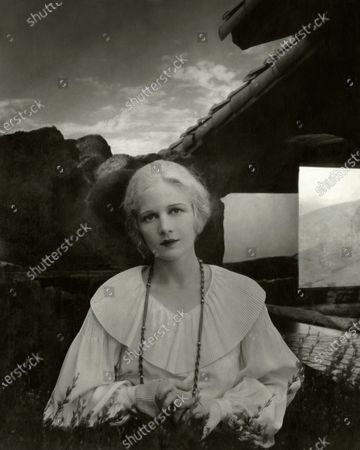 Actress, Ann Harding, wearing a white blouse with a large, pleated bertha collar and full, bishop sleeves with pleated flare cuffs, as well as a long, twist chain necklace, shown from waist up with a tile roof and rocky landscape in the background. Ann Harding