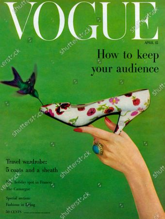 Vogue April 15, 1957 Magazine Cover featuring: Woman's hand holding floral print pump by Dior with humming bird flying around it.