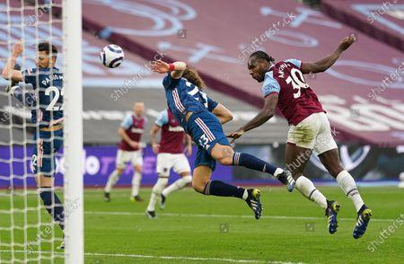 Michail Antonio of West Ham heads the ball ahead of David Luiz of Arsenal
