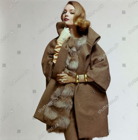 Model Nena von Schlebrugge wearing an ensemble by Monte-Sano & Pruzan: a taupe poncho-shaped coat, in a wool jersey with a tweed look, featuring a high stand tunnel collar and three-quarter length sleeves, and lined in beige-and-white natural fox fur by Fromm Golden Amber Fur; a straight skirt in the same fabric as the coat; a side-tied top in a lighter beige wool jersey. Styled with unattributed accessories: gold bracelets, large gold ring, light beige gloves. Makeup from Estee Lauder: Makeup in Blond, Lipstick in Peppermill. Nena von Schlebrugge