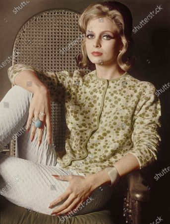 Model Nena von Schlebrugge seated in a caned-back chair. She is wearing a straight, round-necked cashmere sweater featuring a green-and-white Liberty of London print and edged in green; by Braemar. Worn with white stretch pants of a tapestry weave, by Pantino, of acetate and cotton. Styled with a large blue ring from Castlecliff, a gold textured bracelet and tiny pearl earrings. Makeup from Charles of the Ritz: Sun Bronze Coral lipstick and nail polish. Hair by Enrico Caruso. Nena von Schlebrugge