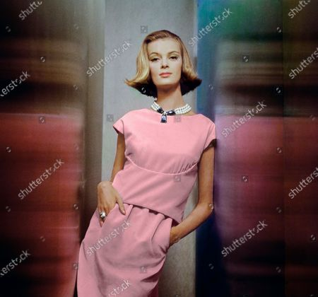 Model Nena von Schlebrugge stands in a close-walled reflective space with her hands in her pockets. She is wearing a two piece pink rayon and cotton velveteen dress with the blouse yoked under the bust line by Larry Aldrich, of Bianchini fabric. Accessories: large fake pearl necklace with blue hanging jeweled pendent by Castlecliff; unattributed jeweled ring. Makeup including Jacqueline Cochran's Flowing Velvet lipstick line in Perky Pink. Nena von Schlebrugge