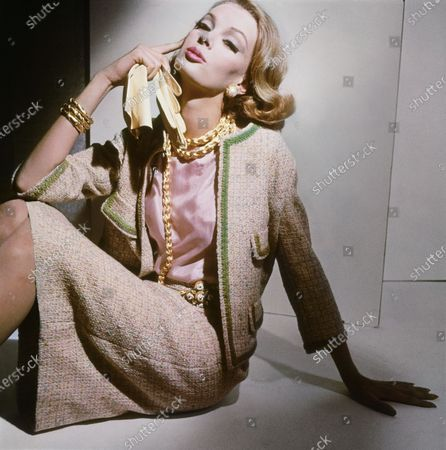 Model Nena von Schlebrugge seated in a studio, wearing a gray wool tweed suit trimmed with green braid around the edges of the jacket's body, pocket flaps, and cuffs, over a pink silk blouse, by Dan Millstein. Worn with gilt chain necklaces by Marvella, gold earrings set with large pearls, gold bangles, and a belt buckled with a quatrefoil of enameled braided buttons. Nena von Schlebrugge