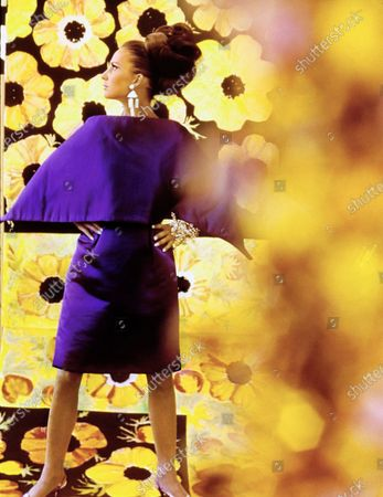 A model standing with her hands on her hips in front of a backdrop of Plexiglass screens painted by New York based artist David Lerner, using a black and yellow floral pattern from a Ken Scott scarf. She is wearing a knee length skirt and shawl of deep purple satin, by Nat Kaplan, made of worsted-and-silk fabric by Couleur. Accessories: rhinestone bracelets by Alice Caviness; rhinestone earrings by Charles Elkaim; Christian Dior sheer stockings; purple silk slingback kitten heels by I.Miller with buckles by Bernard Abrams. Hair by Pierre of the House of Revlon.