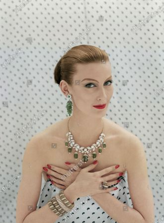 Model Barbara Mullen poses with her hands crossed at her chest in front of a white textile backdrop that is printed with small green paisleys, the same textile wrapped around her torso. She is wearing the India inspired collection of diamond, gold, pearl, emerald, and sapphire jewelry by Van Cleef & Arpels, including cluster earrings, a drop necklace, and striped bangles with a bombe ring set with small stones. Barbara Mullen
