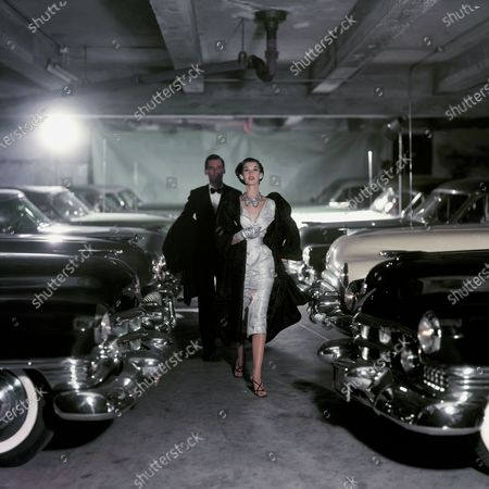 Model Barbara Mullen walks with a male model in a tuxedo through a line of parked cars a parking garage. She is wearing a button front narrow waist sheath dress of white silk brocade by Adele Simpson with a black Russian broadtail lamb coat with a wide collar by Hammer Brand. Accessories: unattributed rhinestone earrings, necklace, and bracelets; unattributed white satin gloves and black sandals. Barbara Mullen