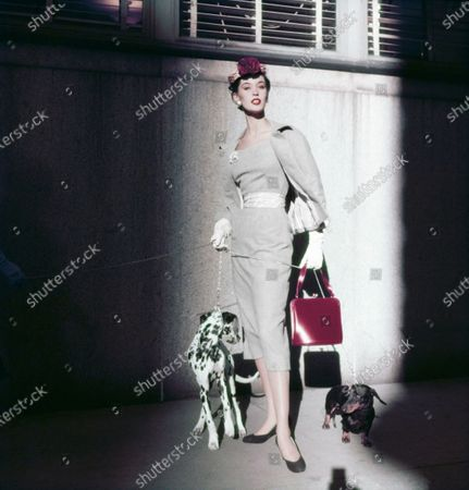 Model Barbara Mullen wearing a grey belted suit by Herbert Sondheim, the striped belt matching the striped lining of the jacket, together with a straw pillbox hat and a red calfskin bag by Koret with two dogs on leashes. Barbara Mullen