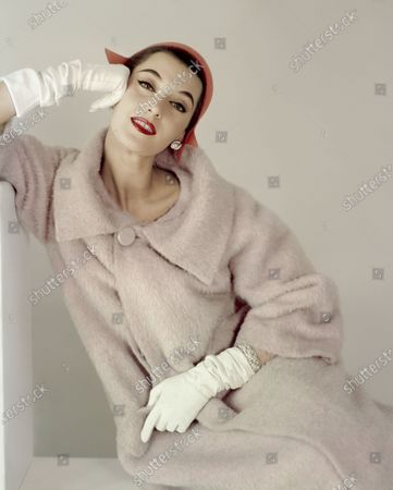 Model Barbara Mullen wearing a pink broad-collared coat from Ben Zuckerman with a coral colored John Frederics hat, white gloves and Verdura jewels.. Barbara Mullen