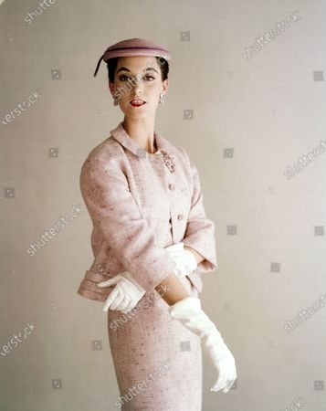 Model Barbara Mullen wearing a pink tweed matchbox jacket and matching sheath dress with a pink hat, all from Hattie Carnegie, worn with white gloves and Verdura jewels. Barbara Mullen