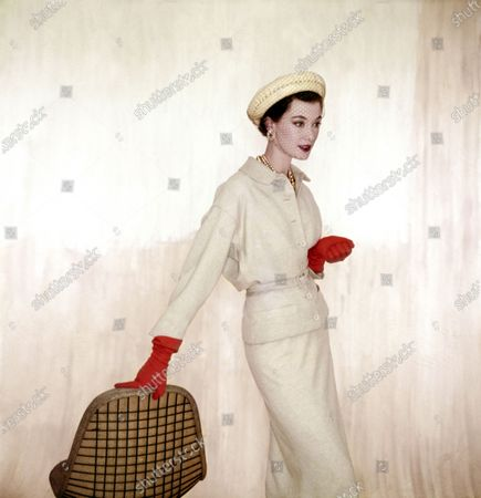Model Barbara Mullen wearing a beige suit and blouse of wool-and-rabbit's- hair by Larry Aldrich with orange Dawnelle gloves and a roller hat by John Frederics. Barbara Mullen