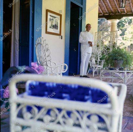 """Venezuelan aristocrat Don Reinaldo Herrera Uslar in his family home, the Hacienda la Vega, in the valley of Caracas in Venezuela. He stands on the side gallery of the house that overlooks the gardens, wearing the """"liqui-liqui,"""" a traditional Venezuelan costume. Reinaldo Herrera Uslar"""