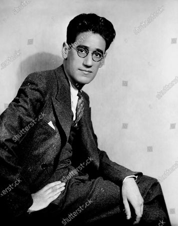 Playwright, director, producer, George S. Kaufman, seated with one hand on hip and the other resting on his knee, wearing a three-piece suit and round, horn-rimmed glasses. George S. Kaufman,  George Kaufman