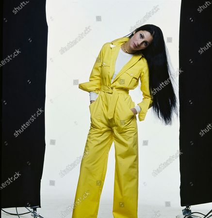 Stock Photo of Singer and actress Cher wearing a bright yellow cotton jumpsuit by Ralph Lauren over a white t-shirt, gold Monet earrings, and Aurea Jewelry Creations twisted gold necklace. Makeup from Helena Rubinstein: Skin Life Deep Moisture Eye Shadow Cream in Lapis Blue and Buttercream. Hair and makeup by Francois of Suga Salon. Cher