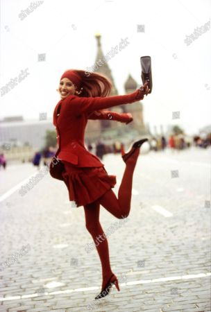 Model Christy Turlington in Moscow's Red Square, wearing a red wool jacket and short pleated skirt by Karl Lagerfeld, with a red headband by Eric Javits, red tights by Wolford, and shoes by Manolo Blahnik. Earrings by Gerard E. Yosca. Bag by Prada. Hair by Oribe at Elizabeth Arden Salon. Makeup by Sonia Kashuk. Christy Turlington