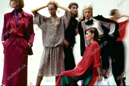 Models (from left to right) Chris Royer, Alva Chinn, Lisa Cooper (standing), Melanie Cain (seated) wearing various ensembles from Oscar de la Renta for Fall 1976. (Two blurred models can be seen in background.) Royer wears a bright silk crêpe de Chine shirt, magenta moire skirt suit of acetate and viscose, Robert Fabrikant earrings, Gudule scarf, and a watch by Zenith-Movado Time. Chinn wears a silk blouson and skirt dinner dress with tiny print flowers, earrings by Ed Samuels, Gindi neck cord, David Webb bangles, and Chestnut Rose lip color. Cooper wears a tucked white polyester chiffon blouse, acetate and rayon satin smoking jacket edged with satin cording, thin black wool flannel pants, floppy satin tie, and Trifari earrings. Cain wears a pink silk tunic slit open at the sides, green sleeveless dress of polyester, purple polyester pants, barrette from St. Laurel by Ben-Hur, and a Kathy Young neck cord. Makeup from Revlon's Polished Ambers Collection. Hair by Mark Pipino. Makeup by Sandra of Xavier, New York. Chris Royer, Alva Chinn, Lisa Cooper, Melanie Cain