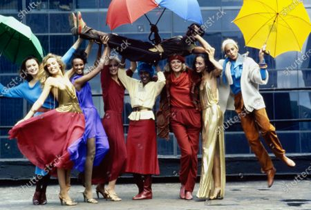 Designer Stephen Burrows, holding red and blue umbrellas, held in the air by nine models on a city street.From left to right:Vibeke Knudsen (with green umbrella) in a blue dress with an asymmetric neckline.Jerry Hall in a pink chiffon dress with a brass mesh spaghetti strap halter bodice.Iman in a blue chiffon jersey blouson dress with an off-the-shoulder neckline.Chris Royer in a red chiffon scarf-tied top and matching side-slit pants.Bethann Hardison in a cream chamois wrap-jacket and red corduroy skirt, with a blue beret.Kirsti Toscani in a shearling jacket over a cowl-necked red sweater and red pants, with a red beret.Pat Cleveland in a cowl-necked, side-slit gold lame evening dress.Alva Chinn, with a yellow umbrella, wearing a white ribbed sweate jacket over a blue sweater-blouse, and brown suede pants.All clothes by Stephen Burrows. Vibeke Knudsen, Jerry Hall, Iman, Chris Royer, Bethann Hardison, Kirsti Toscani, Pat Cleveland, Alva Chinn, Stephen Burrows