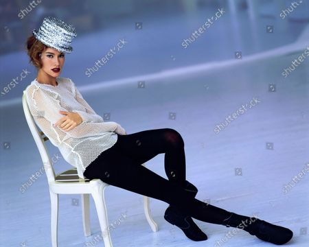 Model Susan Holmes is seated on a chair wearing an ensemble in the Fall 1991 collection by Rei Kawakubo of Comme des Garçons. She wears a stretch wool mesh long-sleeve t-shirt, nylon and polyurethane black tights, silver sequined hat, and black boots, all Comme des Garçons. The chair she sits on is also Comme des Garçons by Rei Kawakubo. Lipstick: Shiseido's Garnet Lipstick. Hair by Didier Malige for Jean Louis David. Makeup by Sonia Kashuk for Aveda. Susan Holmes
