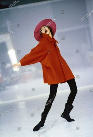 Model Susan Holmes in bias-cut red lamb's wool flared coat, nylon and polyurethane black tights, pinkish-red hat, and black boots, all from Comme des Garçons by Rei Kawakubo, Fall 1991 Collection. Lipstick from Chanel: Rouge à Lèvres Super Hydrabase Creme Lipstick in Image Rose. Hair by Didier Malige for Jean Louis David. Makeup by Sonia Kashuk for Aveda. Susan Holmes