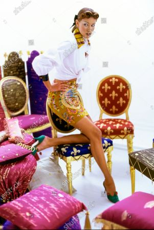 Model Susan Holmes, in a studio with several gilded Louis XVI chairs upholstered by Angele Parlange with fleurs-de-lis and samples of script from 18th-Century calling cards. She is wearing a beaded silk skirt embroidered with 18th-Century patterns, and a white cotton shirt cuffed and collared in striped silk, by Todd Oldham. Shoes by Manolo Blahnik. Susan Holmes