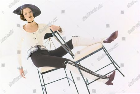 Stock Picture of Model in a studio, seated across a pair of steel chairs designed by Mario Villa, wearing a white cotton scoop-neck jacket trimmed with lace by Geoffrey Beene, a bicorne straw hat by Philip Treacy for Jasper Conran, and knee-high black-and-white leather lace-up boots by Ombeline. Choker by Offray. Cotton and Lycra leggings by Azzura.