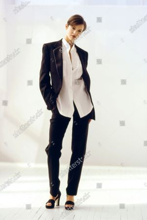Stock Photo of Model Patricia Hartman, in a studio,  wearing a boy's black wool notch-collar tuxedo by After Six over a collarless white Pima cotton shirt from Guess by Georges Marciano. Black high-heel shoes by Prada. Hair by Christiaan. Makeup by Sonia Kashuk for Aveda. Patricia Hartmann