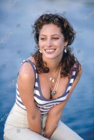 Model Christy Turlington, near water,  wears a blue and white striped cotton bodysuit and oatmeal linen pants by Anvers. Pearl earrings (in ears and on necklace) by Gabrielle Sanchez. Silver necklaces with charms by Roxanne Assoulin for Marc Jacobs/Perry Ellis. Christy Turlington