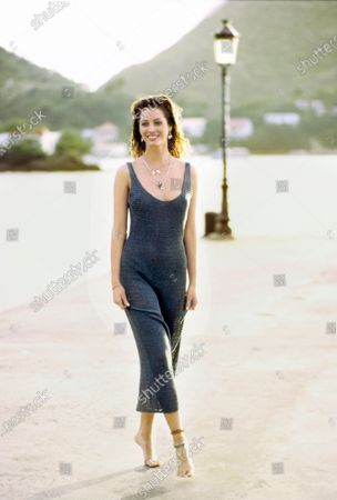 Model Christy Turlington at a waterfront, wearing a gray washed silk knit tank dress by Anvers.Pearl earrings (in ears and on necklace) by Gabrielle Sanchez. Silver necklaces with charms by Roxanne Assoulin for Marc Jacobs/Perry Ellis. Bracelet and anklets by Barbara Small Designs. Christy Turlington