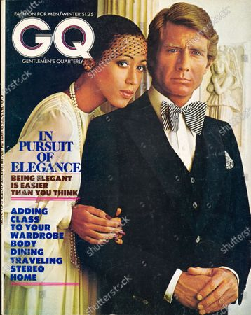 GQ December 01, 1973 Magazine Cover featuring: Female model, wearing a John Anthony dress, with a male model in a Carlo Palazzi vested dinner suit in black velvet, a Madonna tie, and an Echo pocket square. Winter Issue.