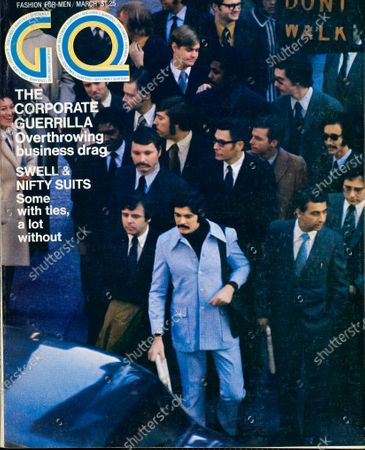 GQ March 01, 1971 Magazine Cover featuring: Male model, standing amid traditionally suited men at a street corner, wearing a Gilbert Feruch cotton shirt-suit.