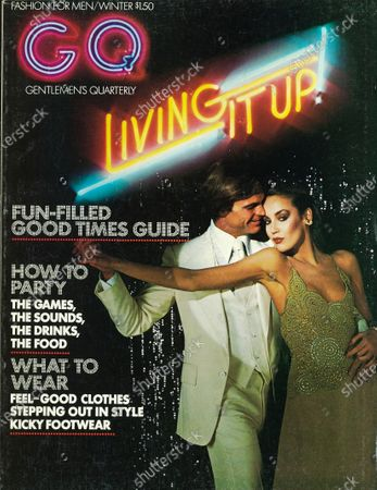 GQ December 01, 1975 Magazine Cover featuring: Red and blue logo in neon superimposed over photo of a couple in a disco setting, he wears a white polyester and wool suit by Arthur Richards, white cotton shirt by Individualized Shirts, and white silk tie by Vicky Davis, her clothes are by Giorgiodi Sant'Angelo, her hair by James Reda and her makeup by Ariella. Winter 1975-1976 Issue.