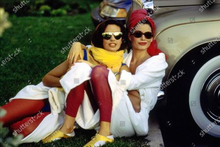 Models Fabienne Terwinghe and Carre Otis leaning against a Rolls-Royce car at The Breakers Hotel in Palm Beach, Florida. Terwinghe, left, wears Norma Kamali's white cotton terry bathrobe with bodysuit and dark red leggings by Giorgio di Sant'Angelo, sunglasses from Christian Roth for Optical Affairs, yellow Echo scarves. Otis, right, wears a white cotton robe from Ralph Lauren, sunglasses from Yorke & Cole, dark red leggings by Giorgio di Sant'Angelo, a red towel around her head, and yellow sneakers from Maud Frizon. Hair by Mitch Barry. Makeup by Sonia Kashuk. Carre Otis, Fabienne Terwinghe