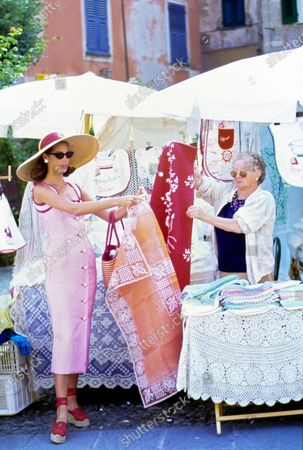Model Christy Turlington looks at Italian lace and linens with a local vendor at an outdoor market in Portofino, Italy. She is wearing a tiny red and white checked silk pique button-front sheath dress by Carolina Herrera. Accessories: straw hat with red ribbon by Norma Kamali; sunglasses by Christian Roth for Optical Affairs; white earrings by Trifari Jewelry; red and white striped bag by Magid; red platform espadrille shoes by Donna Karan Footwear. Hair by Oribe at Elizabeth Arden. Makeup by Sonia Kashuk for Aveda. Christy Turlington