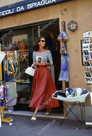 Stock Picture of Model Christy Turlington walks out of a souvenir shop holding some postcards in both hands in Portofino, Italy. She is wearing a navy and white boat necked striped viscose, polyester, and spandex bodysuit by Ungaro Parallele with a full red linen skirt from Vogue Pattern #8331, made from Jerry Brown Fabrics, NYC. Accessories: sunglasses by Christian Roth for Optical Affairs; earrings by Trifari Jewelry; white bag by Magid; white shoes by Manolo Blahnik. Hair by Oribe at Elizabeth Arden. Makeup by Sonia Kashuk for Aveda. Christy Turlington