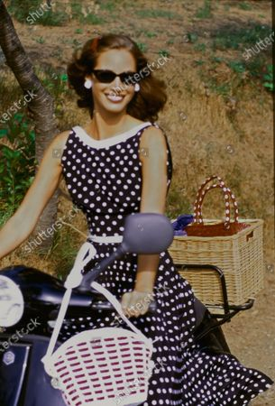 Model Christy Turlington rides a black moped along a grassy hill in Portofino, Italy. She is wearing navy-and-white polka dot sleeveless silk dress with white banded collar and waist and a full skirt by Valentino. Accessories: sunglasses by Christian Roth for Optical Affairs; white earrings by Trifari Jewelry; white and red bag by Magid. Hair by Oribe at Elizabeth Arden. Makeup by Sonia Kashuk for Aveda. Christy Turlington