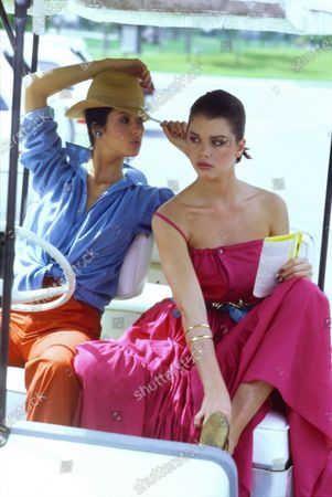 Model Janice Dickinson, left, and her sister Deborah Dickinson, right, sit in a golf cart at the Boca West Resort Golf Course in Boca Raton, Florida. Janice is wearing a blue cotton striped shirt tied at the waist with red-orange pants and a Don Marshall straw hat that she is reaching up to adjust with Celia Sebiri earrings. Deborah is wearing a hot pink cotton sun dress with hemp sandals with gold bangles by Carolee Designs and Monet. Both ensembles by Mic Mac of Paris. Hair by Christiaan. Makeup by Ariella. Janice Dickinson, Debbie Dickinson