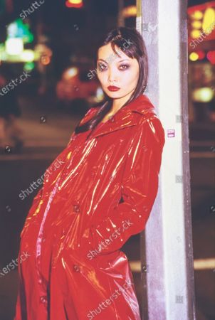 Model Irina Pantaeva leans against a light pole on the city street at night with her hands in her pockets. She is wearing a double-breasted red vinyl slicker by Katharine Hamnett London. Hair by Sam McKnight. Makeup by Mary Greenwell. Irina Pantaeva