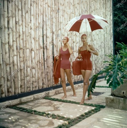 """Two models walk along a stone walkway with a wall of bamboo behind them at the Holmby Hills house of Mrs. Joyce Schutt. The model on the left is wearing a red skirted bathing suit in nylon tricot by Jantzen made from Princeton Knitting, and carrying a red towel. The model on the right is wearing an elasticized bathing suit of knitted wool and nylon with satin stripes by Gantner with a Josef red bag and an unattributed white and red striped umbrella. Both wear Kleinert bathing caps. Makeup including DuBarry Color Glide lipstick in """"Peppermint Pink."""". Ann Todd"""