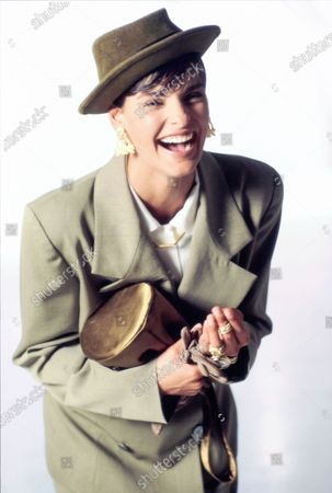 Stock Picture of Model Linda Evangelista laughing, wearing an ensemble from Charlotte Neuville: double-breasted wrapped jacket in melton wool; white rayon blouse. Styled with a green felt hat from Matkins Hats, gold triangle earrings by Mish Jewelry, gold necklace from Annika by Richard Fishman, gold rings by Roxanne Assoulin for Savannah, light brown gloves by Shalimar, and a greenish-gold bag by Prada. Hair by Mitch Barry. Makeup by Sonia Kashuk. Linda Evangelista