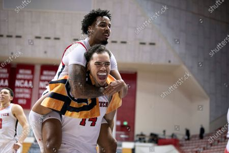 Texas Tech's Kyler Edwards, top, and Marcus Santos-Silva (14) celebrate after a first-round men's college basketball game against Utah State in the NCAA Tournament, at Assembly Hall in Bloomington, Ind